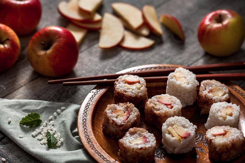 Milchreis Sushi mit Apfel und Vanillesauce. Warum nicht mal süßes Sushi statt der deftigen Variante? Diese süße Sushivariante mit Kokos-Milchreis, Äpfeln und ganz viel Zimt kann man sowohl warm als auch kalt genießen. Foodstyling und Rezept von Purple Avocado