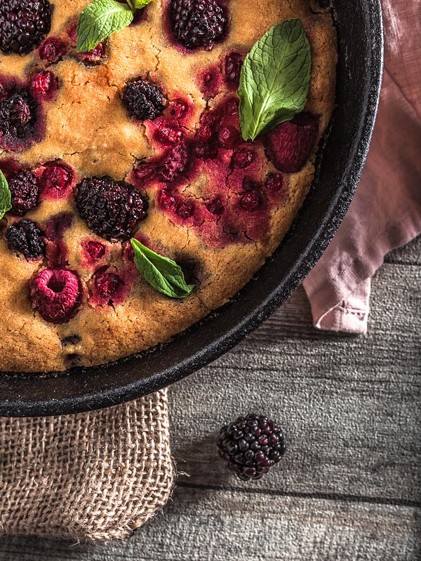 An ethnic recipe for a vegan berry cake freely adapted from a recipe of the Ethno Cookbook by Karolina Przybylska with lots of fresh berrys and maple syrup.