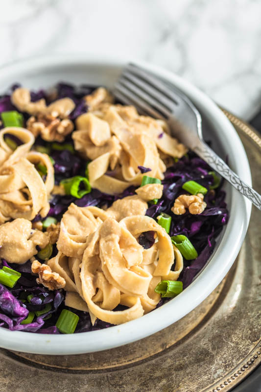 Fettuccine in a creamy hummus sauce with crisp red cabbage and roasted walnuts. Enjoyable warm and cold - perfect salad for to go. Recipe and foodstyling by purple avocado