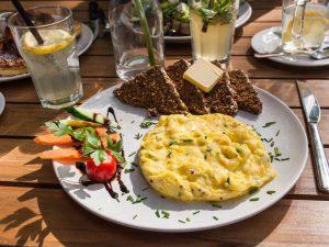 Rührei mit Schwarzbrot, Butter und Salat im Café von der Motte in Hamburg, Ottensen