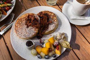 Pancakes mit Bacon und Ahornsirup im Café von der Motte in Hamburg, Ottensen. Dazu gibt es einen Obstsalat