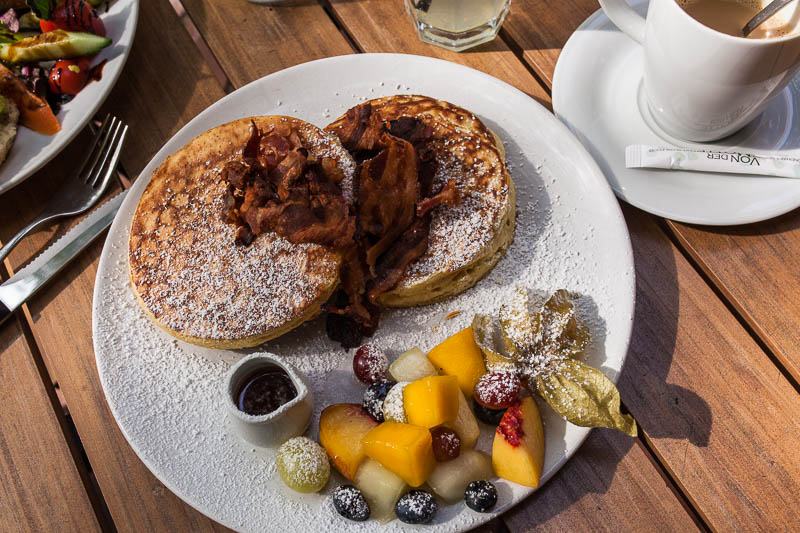 Thick and fluffy pancakes with maple syrup, bacon and fruit salad in Hamburg at Von der Motte