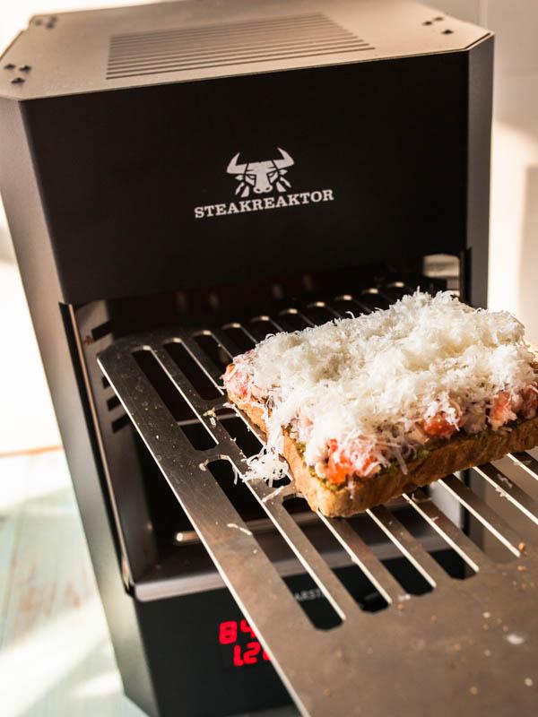 Bruschetta mit Parmesankruste wird in den Steakreaktor geschoben.