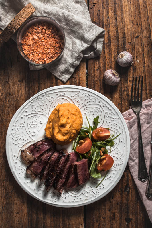 Recipe for garlic maniacs: Creamy garlicky mashed sweet potatoes. The perfect side for any hearty meal. #vegan #sides #potato #recipes #winter #autumn #steak