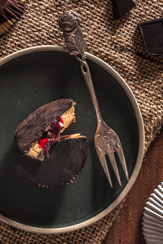 Recipe for Reese's inspired peanut butter jelly cups. Peanut butter, jam and dark chocolate in a parliné shape. 5 ingredients only and kind of healthy-ish and vegan. #dessert #sweet #no #valentines #recipe #vegan #healthy
