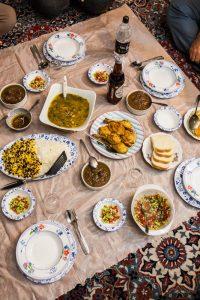Traditionelle Iranische Speisen am Boden auf einer Wachstischdecke serviert
