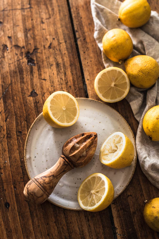 Still life of lemons and a lemon juicer on a rustic wooden counter top