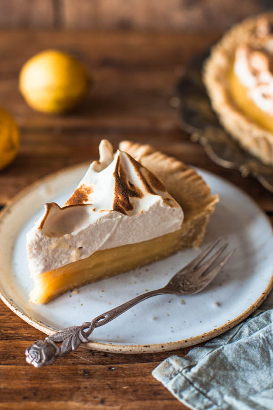 One piece of vegan lemon meringue pie placed on a handmade white plate. The overall feeling is very rustic and cozy.