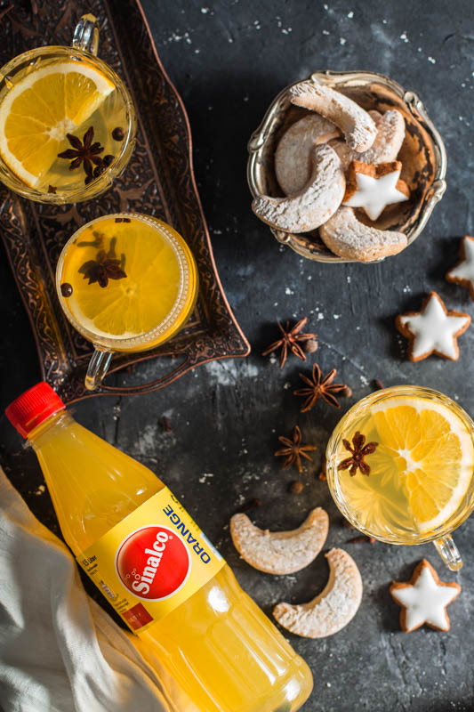 A festive setup on a dark gray surface containing three crystal glasses filled with mulled white wine, a bowl of Christmas cookies and a bottle of orange lemonade from Sinalco