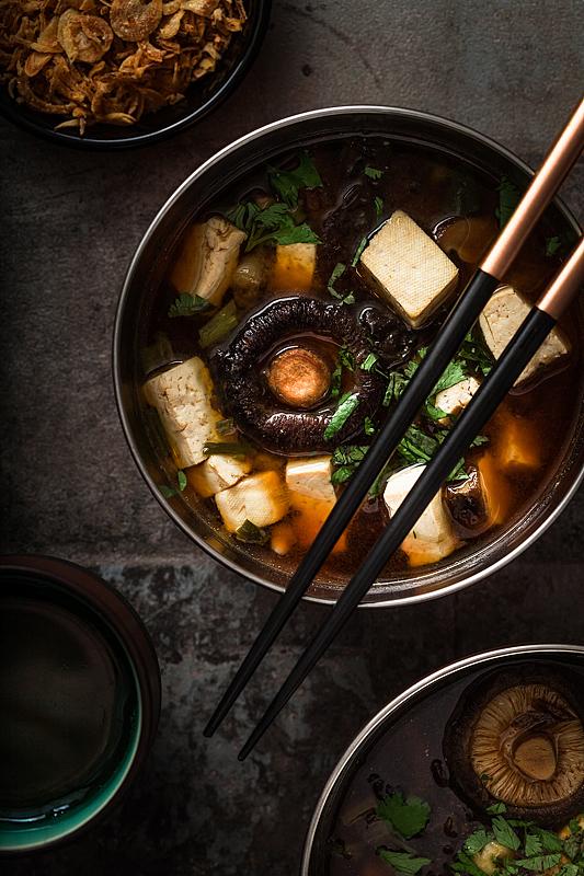 Miso Suppe in einer Schüssel mit Tofu, Pilzen, Kräutern und einem Paar Essstäbchen
