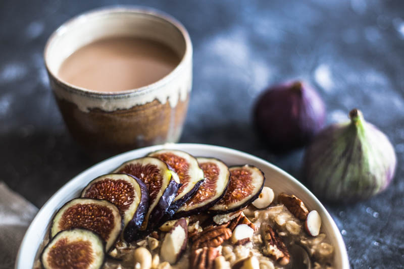 Cooking rolled oats in microwave - a healthy breakfast bowl with chopped nuts and sliced figs