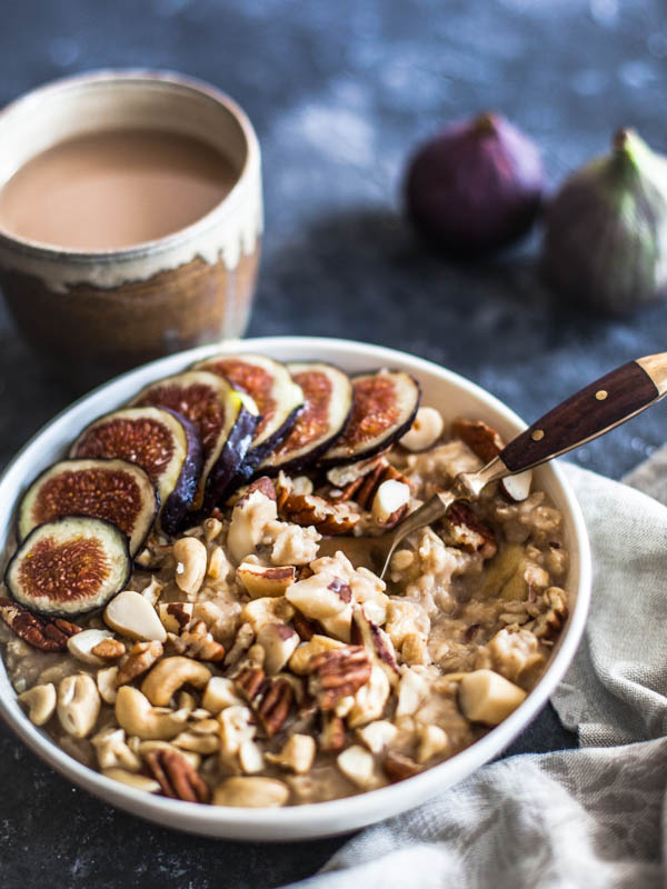 A bowl of microwave oats served with chopped nuts and fresh slices of figs