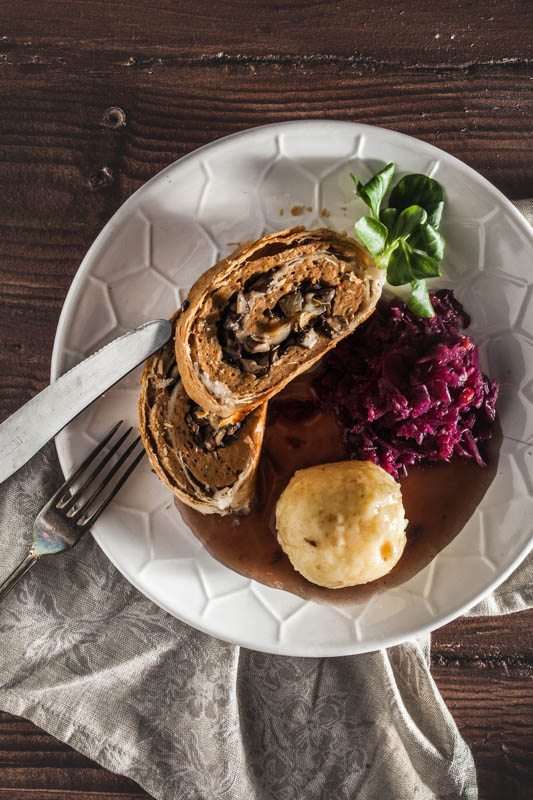 2 slices of vegan seitan roast on a plate served with dumplings and red cabbage