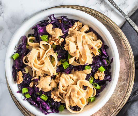 Cremige Hummus Nudeln mit Rotkohl und Walnüssen. Aus Kichererbsen und Sesampaste machen wir eine kräftige Hummus-Sauce für vegane Fettuccine. Schmeckt auch herrlich am zweiten Tag als Salat - perfekt für unterwegs. Rezept und Foodstyling von Purple Avocado.