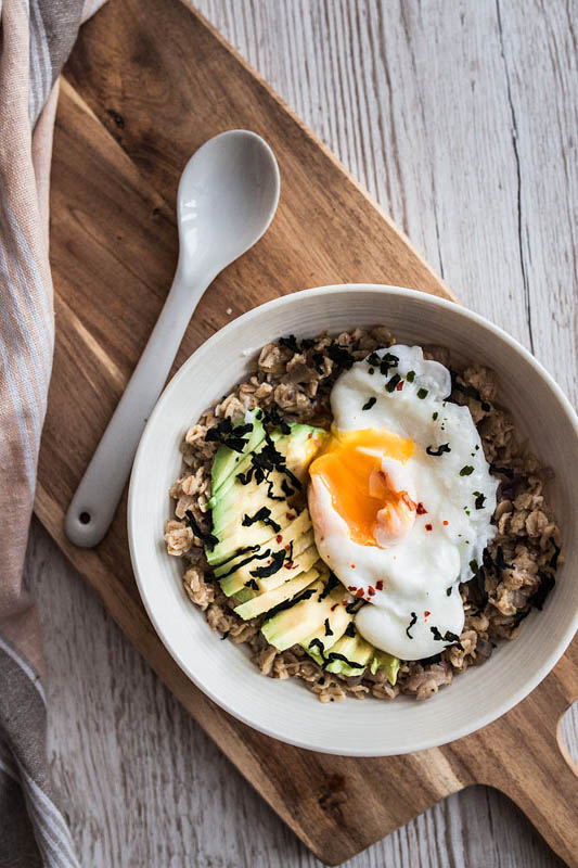 Breakfast becomes dinner with this savoury porridge with avocado, poached egg and roasted sea weed. Recipe and food styling from purple avocado / sabrina dietz.