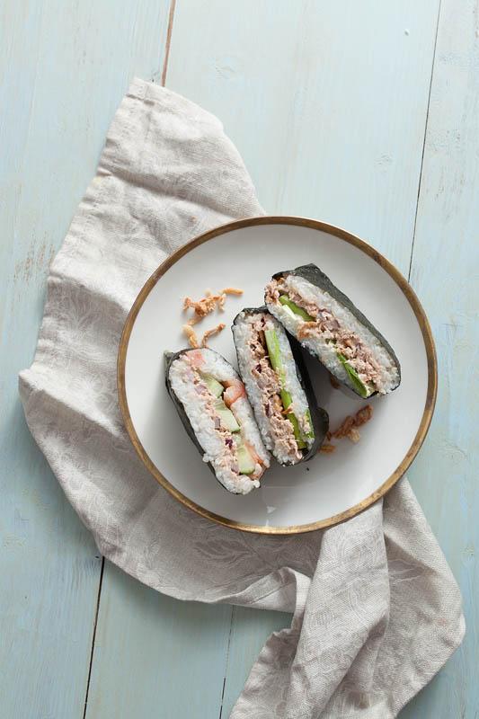 Tunfisch Onigirazu Füllung - 3 Reissandwiches auf einem Teller mit Goldrand drapiert