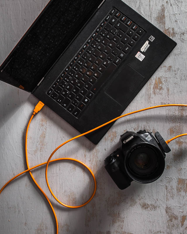 Laptop and camera connected with a tether cable