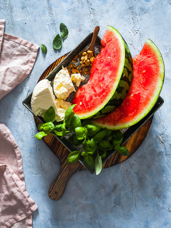Wassermelonen, Feta, Basilikum und Pinienkerne auf einem Teller angerichtet. Ingredient-Shot