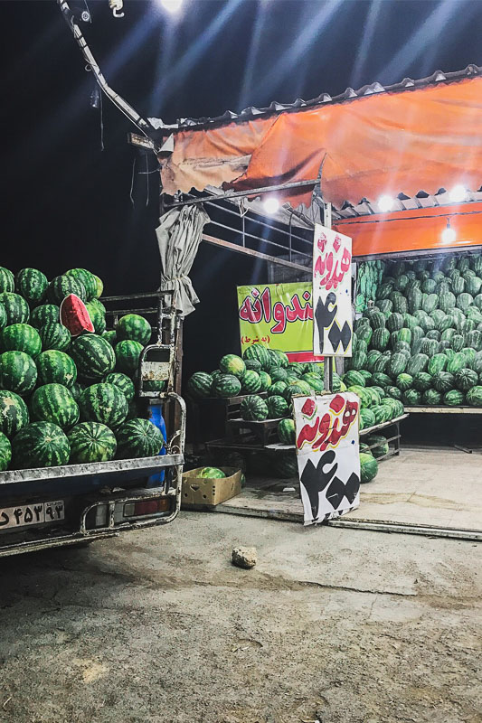 Dozens and dozens of watermelons at a booth