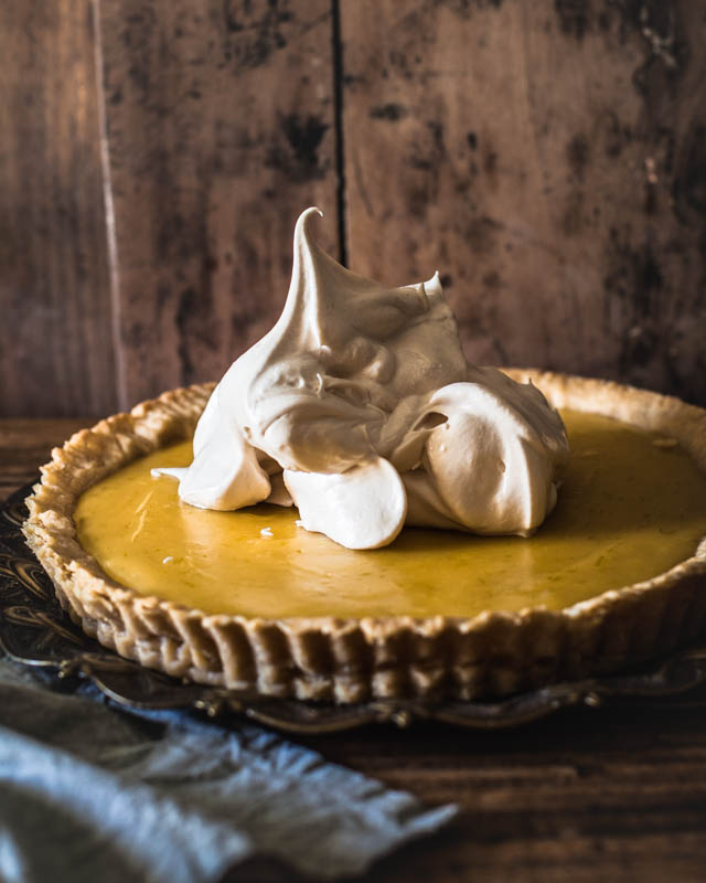 A big scoop of meringue dropped on the cooled down lemon pie. The meringue looks very stiff and fluffy.