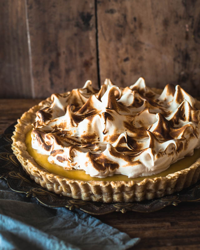 Lemon Meringue Pie on a rustic plate and surface