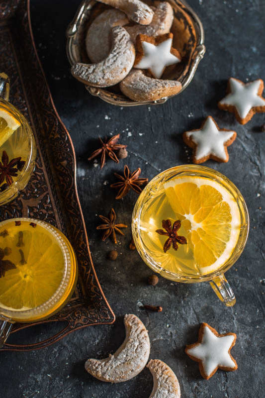 Homemade german mulled wine served in pretty crystal glasses and decorated with orange slices and star anise. Christmas cookies are spread around the glasses and served in a small bowl.