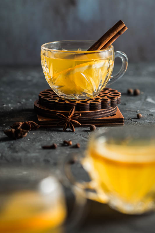 A crystal glass filled with mulled white wine and decorated with a stick of cinnamon