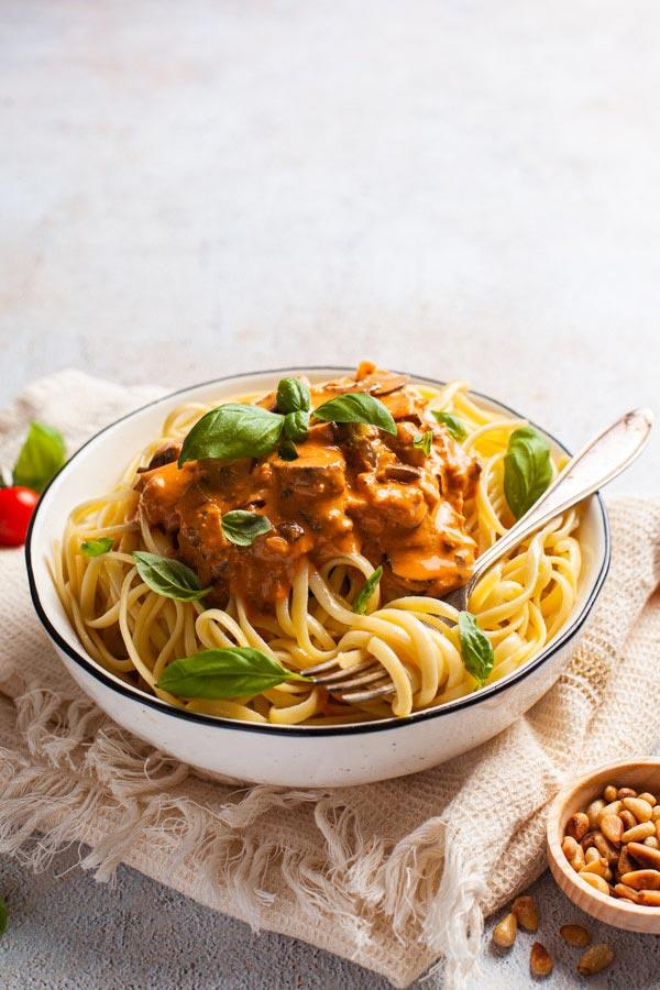 Eine Schüssel Spaghetti mit cremiger, roter Sauce vor einem hellen, texturierten Fotountergrund aus Vinyl von Pa Backdrops