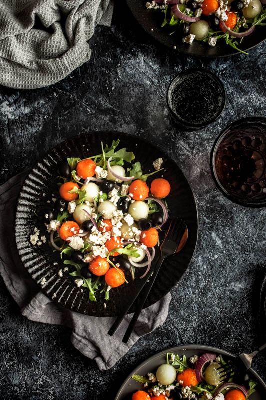 Moody Food Photography auf einem dunklen Vinyl Backdrop von PA Backdrops. Das Hauptmotiv ist ein bunter Salat mit Melonenbällchen